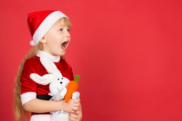 Conocer la navidad con su amiga. niña linda vestida como santa mirando a otro lado sorprendido con la boca abierta sosteniendo su conejo de juguete