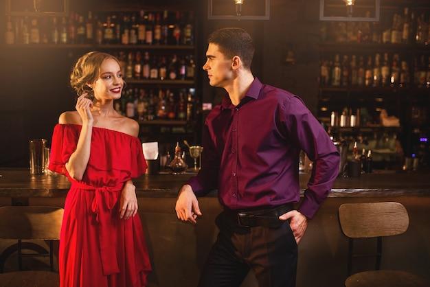 Conocido en el bar, hermosa mujer en vestido rojo coquetea con el hombre detrás del mostrador. fecha en discoteca, pareja atractiva se divierte juntos en el interior