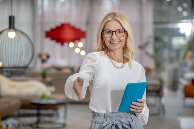 Conocido. sonriente mujer exitosa en vasos sosteniendo una tableta en una mano, extendiendo su mano hacia adelante para salir.
