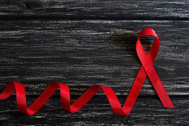 Conocimiento de la cinta roja de primer plano en el fondo de la mesa de madera negra para la campaña del día mundial del sida