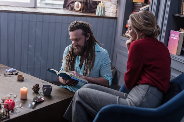 Conocimiento del futuro. niza adivino inteligente leyendo un libro especial mientras está sentado junto con su visitante
