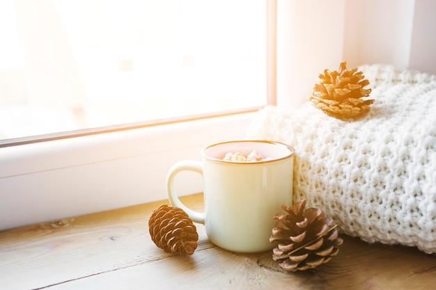Conos y chocolate caliente cerca de la bufanda y la ventana