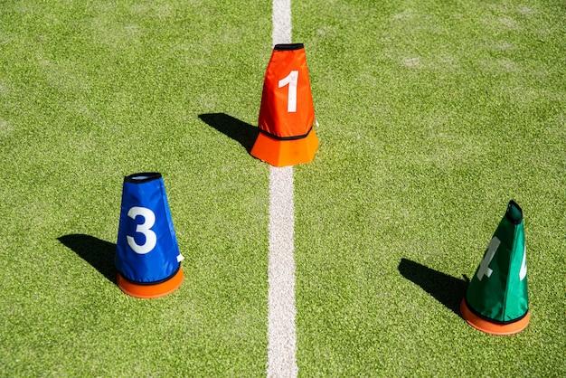 Conos deportivos para el entrenamiento en una cancha de césped artificial.