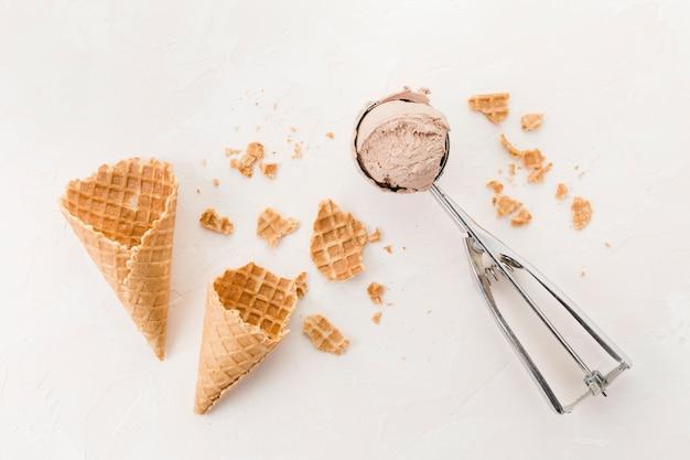 Conos de galleta crujientes y helado sobre fondo claro