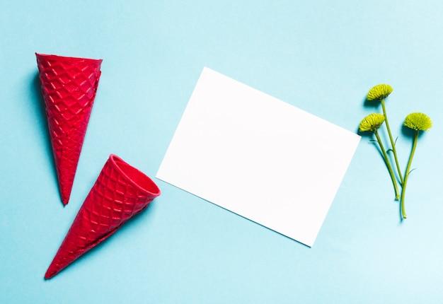 Conos de galleta y hoja de papel sobre fondo claro