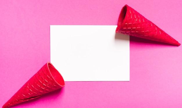 Conos de helado crujientes y hoja blanca sobre fondo rosa