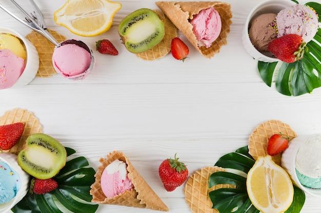 Conos de helado, frutas y hojas verdes.