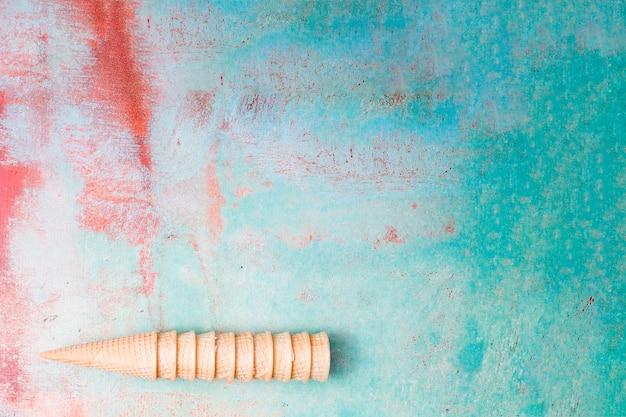 Conos de helado de obleas en blanco reunidos entre sí sobre fondo multicolor