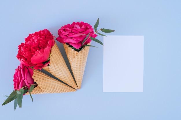 Conos de helado planos laicos con peonía rosa y rosas y blanco claro en blanco