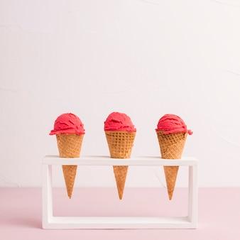 Conos de helado rojos en soporte.