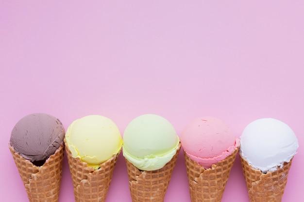 Conos de helado sabores en mesa rosa