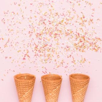 Conos de helado vacíos y aderezos de colores.