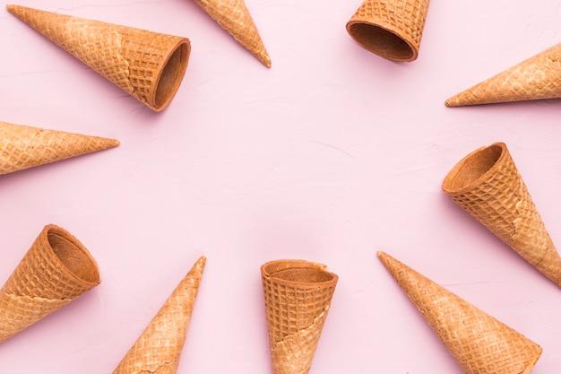Conos de helado vacíos de la galleta del verano en fondo rosado