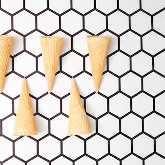 Conos de helado de waffle sobre fondo hexagonal