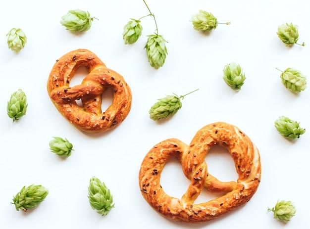 Conos de lúpulo y pretzels en un fondo blanco aislado.