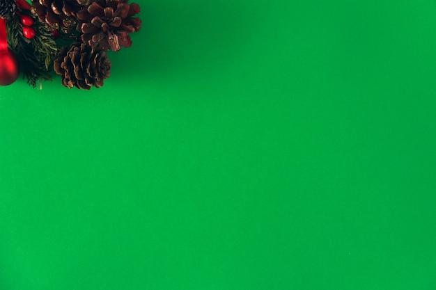 Conos de pino de navidad con cinta roja sobre fondo verde. copie el espacio. enfoque selectivo.