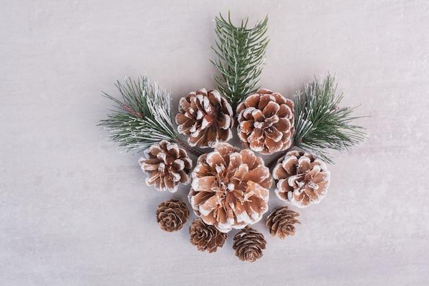 Conos de pino y ramas en mesa blanca