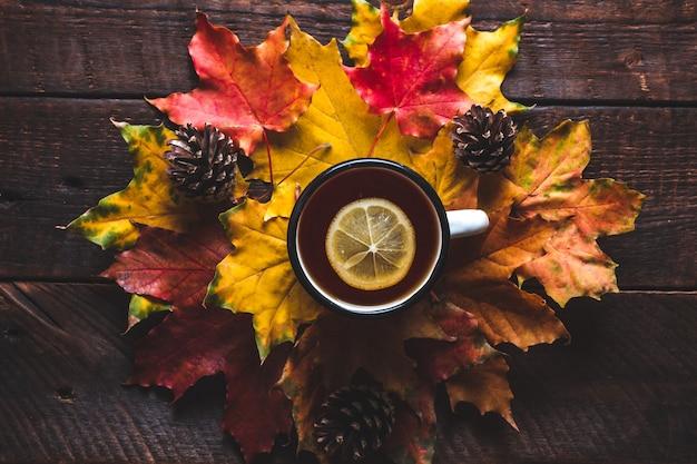 Conos de pino y una taza de té caliente con limón. bebidas de otoño concepto de otoño
