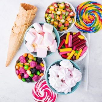 Conos y piruletas cerca de dulces en cuencos
