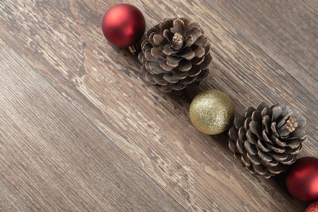 Conos de roble natural sobre una plataforma de madera con adornos brillantes alrededor