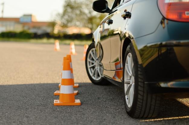Conos de tráfico naranja y coche, lección en concepto de escuela de conducción.