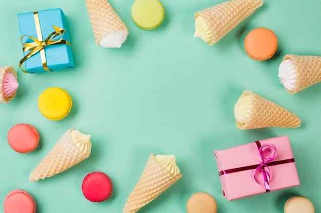 Conos de waffle; macarrones y cajas de regalo envueltas sobre fondo verde menta
