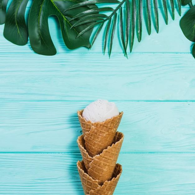 Conos y bola de helado cerca de hojas