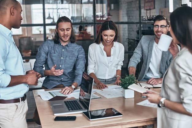 Conseguir los mejores resultados juntos. grupo de jóvenes empresarios comunicándose y sonriendo mientras trabaja en la oficina