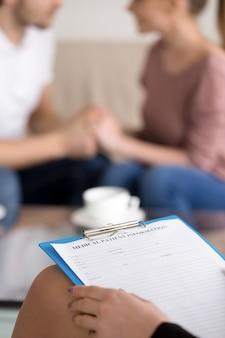 Consejería de pareja. mujer psicoterapeuta con portapapeles y feliz familia reconciliada.