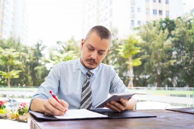 Consejero masculino concentrado editando datos en papel.