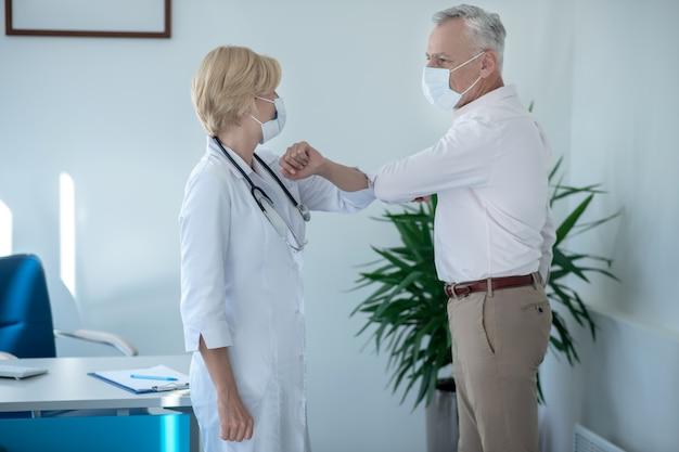 Consejo médico. paciente varón canoso tocando los codos con la doctora rubia