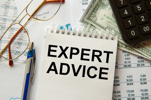 Consejos expertos se escribe en un bloc de notas, en un escritorio de oficina con accesorios de oficina.