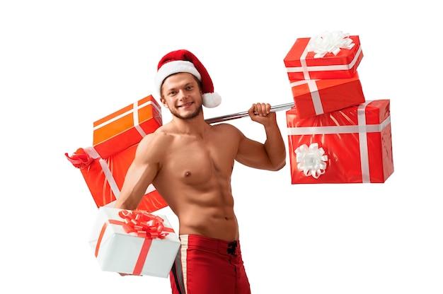 Consejos de fitness de santa. retrato de un papá noel desgarrado sin camisa que ofrece una gran caja de regalo mirando hacia otro lado sonriendo felizmente, 2018, 2019.