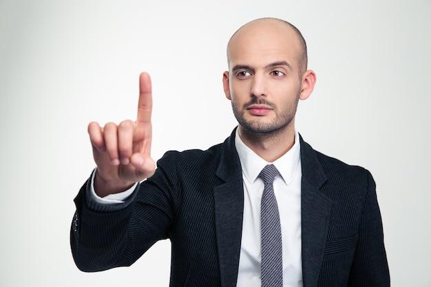Consentido apuesto joven empresario en ropa formal tocando copyspace con el dedo sobre la pared blanca