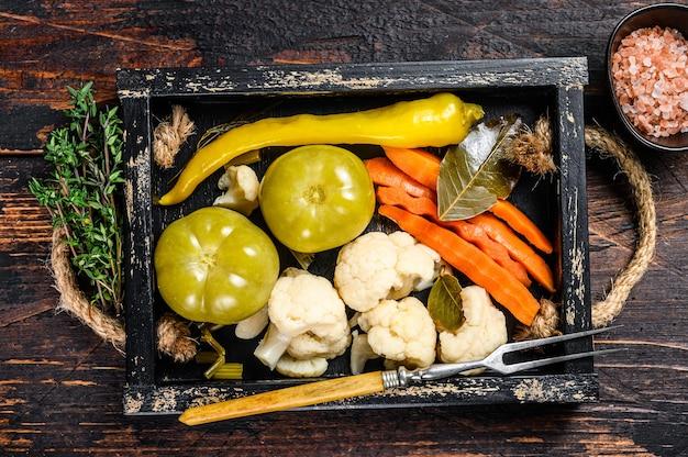 Conservas caseras de verduras adobadas y encurtidos en bandeja de madera.