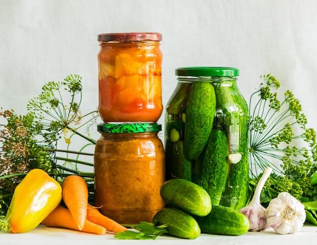 Conservas fermentadas o enlatadas diversas verduras calabacín zanahorias pepinos en frascos de vidrio en la mesa