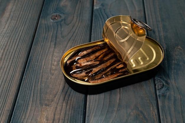 Conservas de pescado en salsa conservar en mesa de madera oscura.
