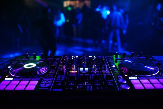Consola de dj para mezclar música con gente borrosa bailando en una fiesta de discoteca
