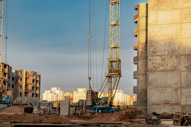 Construcción de una casa de estructura de paneles al atardecer utilizando una grúa torre. luz de fondo. trabajar de noche en la construcción de un edificio residencial.