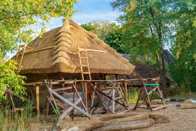 Construcción de casa con techo de paja bajo el estilo antiguo ucraniano en el pueblo de pirogovo