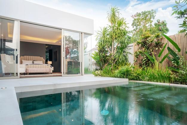 Construcción de casas o casas diseño exterior e interior que muestra una villa con piscina tropical con jardín verde