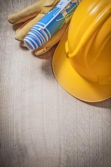 Construcción de casco de cuero guantes protectores dibujos de ingeniería azul en concepto de construcción de tablero de madera.