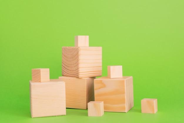 Construcción de cubos de madera sobre fondo verde con espacio de copia. composición de la maqueta para el diseño