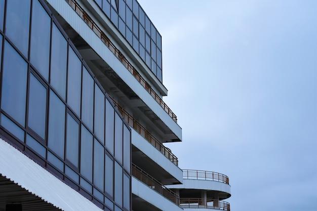 La construcción de un edificio moderno con estacionamiento de vidrio y balcones largos.