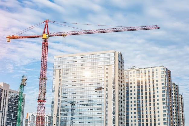Construcción de grúas y rascacielos de vidrio con reflejo de sol, venta de inmuebles para la población.