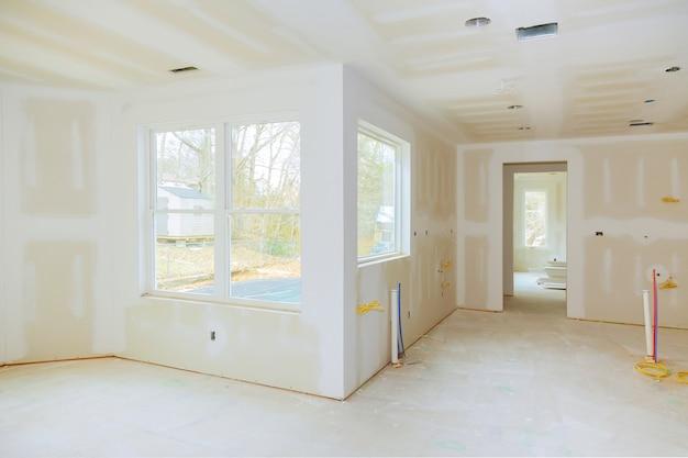 Construcción interior del proyecto de vivienda con paneles de yeso instalados y parcheados sin pintura aplicada