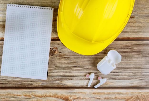 Construcción de oficinas de mantenimiento de ingenieros, casco con auriculares inalámbricos de bloc de notas en tablero de madera vintage