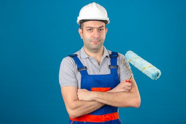 Construcción serio buscando trabajador en uniforme y casco de seguridad con manos cruzadas sosteniendo el rodillo de pintura en azul aislado