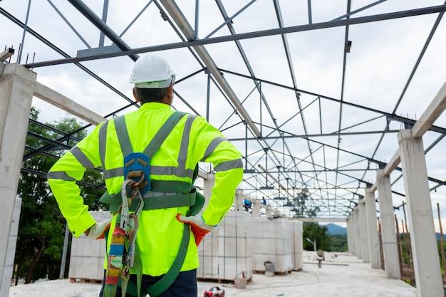 Construcción de técnico ingeniero senior asiático con arnés de seguridad y línea de seguridad trabajando en construcción