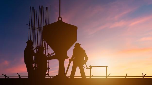 Construcción de trabajadores de silueta equipos vertiendo hormigón. sitios de construcción a través de sitios de construcción borrosos al atardecer